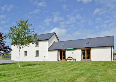Llanlliwe Cottage, Henllan Amgoed is a four bedroom three bathroom barn conversion for eight near Narberth. The open plan living room has vaulted beamed ceiling, farmhouse kitchen & sitting area with French doors onto patio with rural views.