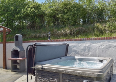 The barbecue area & hot tub at Ty Hapus, Dwrbach